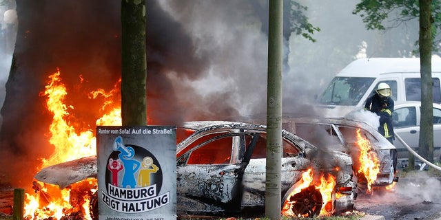 German firefighters put out a number of cars that have been set ablaze near the G-20 summit in Hamburg, Germany, on Friday, July 7, 2017.