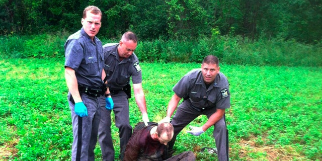 Police stand over David Sweat after he was shot and captured near the Canadian border Sunday, June 28, 2015, in Constable, N.Y. Sweat is the second of two convicted murderers who staged a brazen escape three weeks ago from a maximum-security prison in northern New York. His capture came two days after his escape partner, Richard Matt, was shot and killed by authorities. (AP Photo)