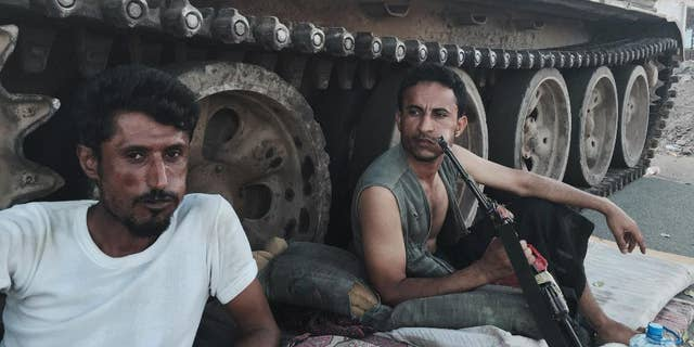 FILE - In this March 21, 2015, photo, Members of a militia group loyal to Yemen's President Abed Rabbo Mansour Hadi, known as the Popular Committees, chew qat as they sit next to their tank, guarding a major intersection in Aden, Yemen. Once hailed by President Barack Obama as a model for fighting extremism, the U.S. counterterrorism strategy in Yemen has all but collapsed as the country descends into chaos, according to U.S. and Yemeni officials. (AP Photo/Hamza Hendawi, File)