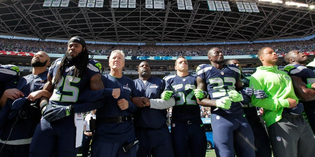 Seattle Seahawks players and coaches stand and link arms during the playing of the National Anthem.