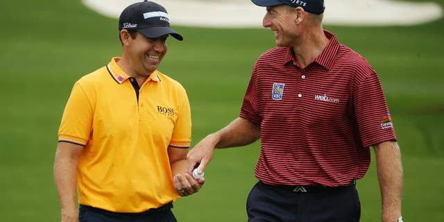 Jim Furyk, right, gives Erik Compton a ball before teeing off at the eighth hole during a practice round for the Masters golf tournament Monday, April 6, 2015, in Augusta, Ga. (AP Photo/Charlie Riedel)