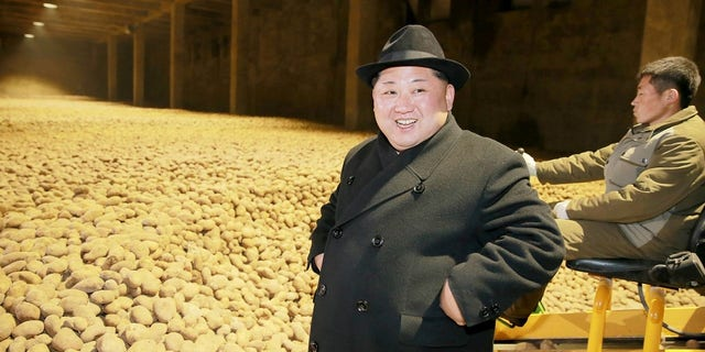 Kim stands in front of potatoes at a potato flour factory inspection.