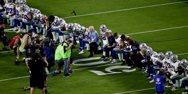 Dallas Cowboys owner Jerry Jones, center, takes a knee with the team prior to an NFL game against the Arizona Cardinals.