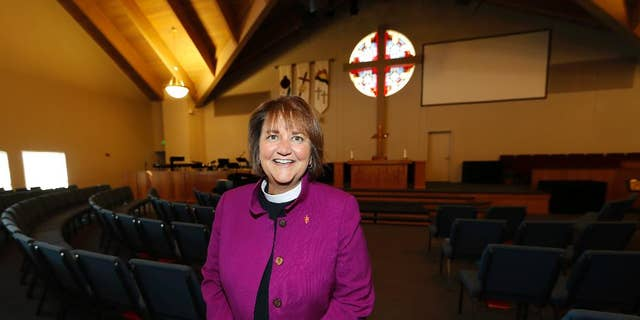 In this Wednesday, April 19, 2017, photo, Bishop Karen Oliveto poses for a photo in the sanctuary of a United Methodist Church in Highlands Ranch, Colo. The top court in the United Methodist Church on Tuesday, April 25, will consider whether the election of Oliveto, the first openly lesbian Methodist bishop, violated church law barring clergy who are ``self-avowed practicing homosexuals.'' (AP Photo/David Zalubowski)