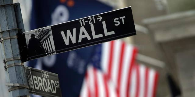 FILE - This Oct. 2, 2014 file photo shows a Wall Street sign adjacent to the New York Stock Exchange, in New York. U.S. stock prices are edging higher in early trading Tuesday, April 7, 2015, putting the market on track for its third gain in a row. (AP Photo/Richard Drew, File)