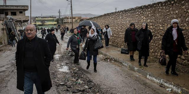 Saturday, December 24, 2016: Christians walk in the rain to attend Christmas Eve's Mass in the Assyrian Orthodox church of Mart Shmoni, in Bartella, Iraq.