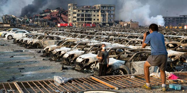 In this photo taken Thursday, Aug. 13, 2015, a man takes photo for another near charred remains of new cars at a parking lot near the site of a warehouse explosion in northeastern China's Tianjin municipality.  People recently punished in China's campaign against online rumors include those who circulated an inflated death toll in the Tianjin blasts and who alleged a man committed suicide because of the country's stock market woes, state media reported Monday, Aug. 31, 2015.(AP Photo/Ng Han Guan)