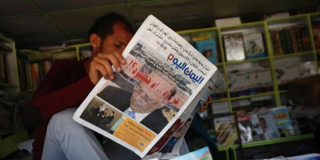 """A Yemeni man reads a newspaper featuring the front page with a photograph of former President Abed Rabbo Mansour Hadi, and a headline in Arabic that reads, """" did they release him or kidnap him?"""" in Sanaa, Yemen, Sunday, Feb. 22, 2015. Virtually powerless for months, Yemen's overthrown President Hadi appeared ready to disappear from the country after fleeing Shiite rebels who held him captive in his own home. But the soft-spoken technocrat who long has avoided the limelight stepped back into it Saturday by renouncing his own resignation and challenging the Shiite Houthi rebels who hold control the capital and large parts of the country. (AP Photo/Hani Mohammed)"""