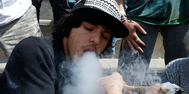 April 18, 2015: Partygoers listen to music and smoke marijuana on one of several days of the annual 4/20 marijuana festival, in Denver's downtown Civic Center Park. The annual event is the second 4/20 marijuana celebration since retail marijuana stores began selling in January 2014.