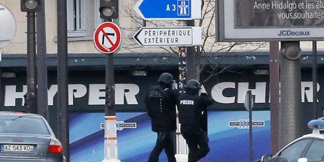 Jan.9, 2015: Police officers walk in front of a hostage-taking situation at a kosher market, seen in blue in background, in Paris, Friday . A police official says the man who has taken at least five people hostage in a kosher market in Paris appears linked to the newsroom massacre earlier this week that left 12 people dead.