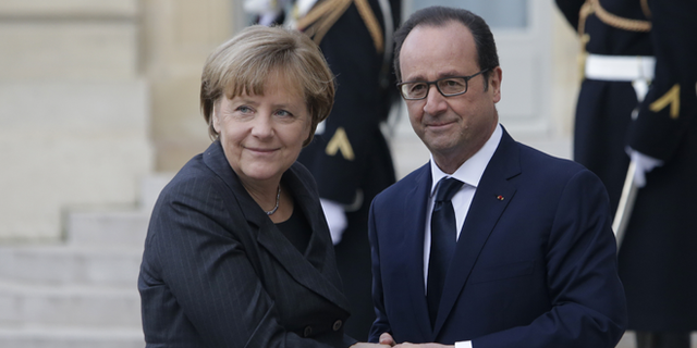 Jan. 11, 2015: French President Francois Hollande welcomes German Chancellor Angela Merkel, left, as she arrives at the Elysee Palace, Paris.