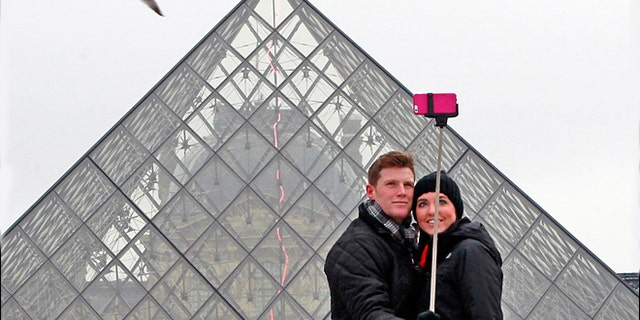 FILE -- Jan. 6, 2015: Chris Baker and Jennifer Hinson from Nashville, Tennessee, use a selfie stick in front of the Louvre Pyramide in Paris.
