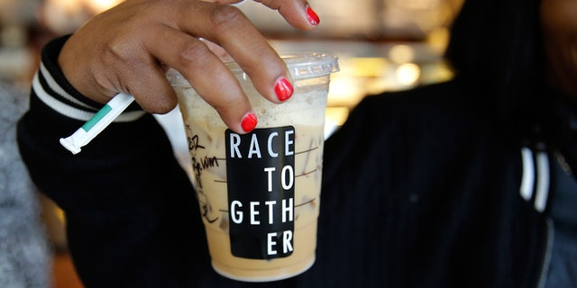 """March 18, 2015: Larenda Myres holds an iced coffee drink with a """"Race Together"""" sticker on it at a Starbucks store in Seattle. Starbucks CEO Howard Schultz announced earlier in the day at the company's annual shareholder meeting that participating baristas at stores in the U.S. will be putting the stickers on cups and also writing the words """"#RaceTogether"""" for customers in an effort to raise awareness and discussion of race relations."""