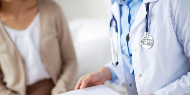 Female doctor holding application form while consulting patient