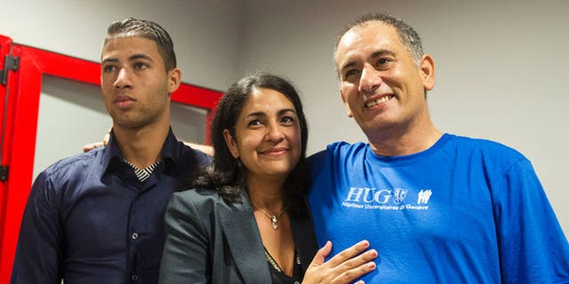 """Felix Baez, a member of the International Contingent Brigade """"Henry Reeve"""", who was infected with Ebola in Sierra Leone, poses for a photo with his wife Vania Ferrer and his son Alejandro Baez during a news conference in Havana December 6, 2014."""