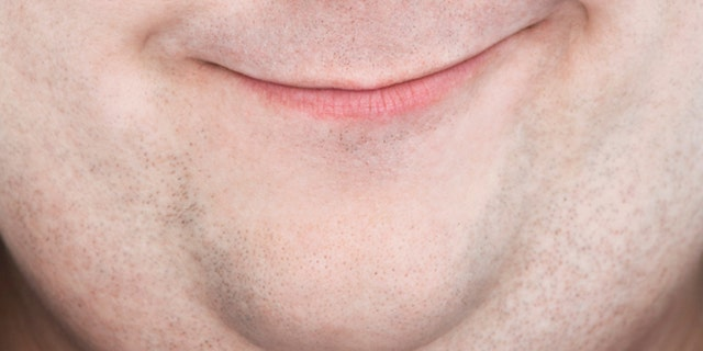 Extreme closeup portrait of an overweight man's face with funny expression