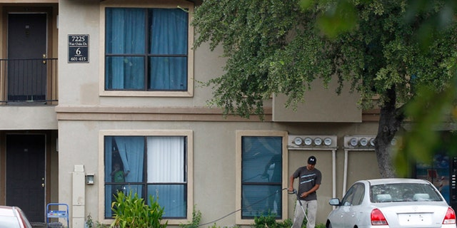 Oct. 2, 2014: A worker washes the sidewalk in front of the apartment unit at The Ivy Apartments, where a man diagnosed with the Ebola virus was staying in Dallas. (REUTERS/Mike Stone)