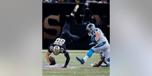 New Orleans Saints tight end Jimmy Graham (80) is upended as Carolina Panthers middle linebacker Luke Kuechly closes in on a reception in the first half of an NFL football game in New Orleans, Sunday, Dec. 7, 2014. (AP Photo/Bill Haber)