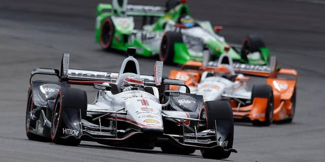 Helio Castroneves, of Brazil, leaves his pit after his first pit stop during the Grand Prix of Indianapolis auto race at Indianapolis Motor Speedway in Indianapolis, Saturday, May 9, 2015.  (AP Photo/AJ Mast)