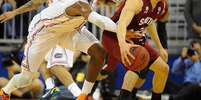 Florida forward Will Yeguete (15) tries to knock the ball out of the hands of South Carolina's Michael Carrera (24) during the first half of an NCAA college basketball game in Gainesville, Fla., Wednesday, Jan. 30, 2013.  (AP Photo/Phil Sandlin)