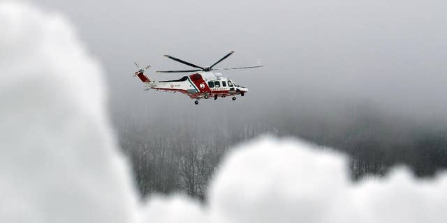 A Coast Guard rescue helicopter flies to the avalanche-hit area where a hotel is buried under the snow, near Farandola, central Italy, Friday, Jan. 20, 2017. Rescue crews located up to eight people alive in the kitchen of an avalanche-crushed hotel on Friday, an incredible discovery that boosted spirits two days after the massive snow slide buried around 30 people in the resort. (AP Photo/Gregorio Borgia)