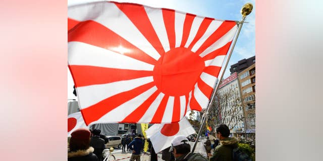 "Members of a nationalist group hold a ""Rising Sun"" flag at a rally in Tokyo on February 22, 2013 over the disputed Takeshima/Dokdo islands"