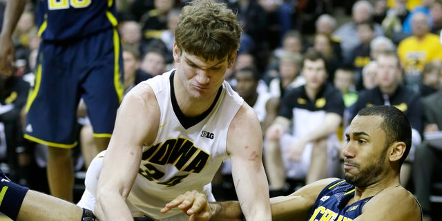 Iowa center Adam Woodbury, left, fights for a loose ball with Michigan forward Jon Horford during the second half of an NCAA college basketball game, Saturday, Feb. 8, 2014, in Iowa City, Iowa. Iowa won 85-67. (AP Photo/Charlie Neibergall)