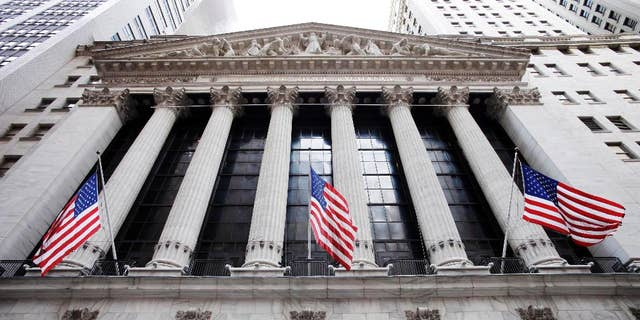FILE - In this Feb. 10, 2011 file photo, American flags fly in front of the New York Stock Exchange, in New York. U.S. stocks were little changed in early trading Thursday, April 9, 2015, as investors assessed company earnings. Energy stocks were among the early gainers as oil recouped some of its losses from a big sell-off on Wednesday. (AP Photo/Mark Lennihan, File)