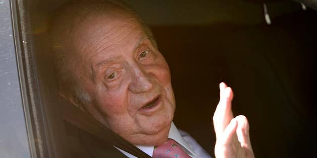 Spain's King Juan Carlos waves on arrival to the Quiron University Hospital in Madrid on September 24, 2013.