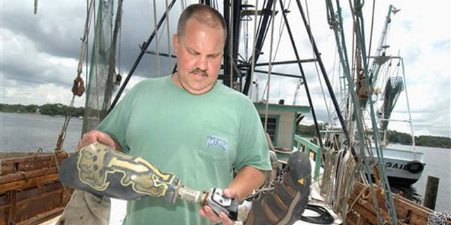 June 7, 2012: Matt Willingham, owner of the shrimp boat Michele Dawn, looks for identifying features on a prosthetic leg at his dock in Valapraiso, Fla.