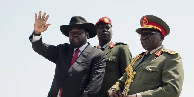 In this Thursday, July 9, 2015, a photo is submitted, South Sudan's President Salva Kiir, left, accompanied by Army Chief of Staff Paul Malong, right waves during an Independence Day ceremony in the capital Juba, South Sudan.