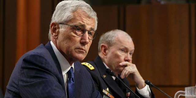 Defense Secretary Chuck Hagel, left, and Army Gen. Martin Dempsey, chairman of the Joint Chiefs of Staff, appear before the Senate Armed Services Committee, the first in a series of high-profile Capitol Hill hearings that will measure the president's ability to rally congressional support for President Barack Obama's strategy to combat Islamic State extremists in Iraq and Syria, in Washington, Tuesday, Sept. 16, 2014. Obama last week outlined his military plan to destroy the extremists, authorizing U.S. airstrikes inside Syria, stepping up attacks in Iraq and deploying additional American troops, with more than 1,000 now advising and assisting Iraqi security forces to counter the terrorism threat.  (AP Photo/J. Scott Applewhite)