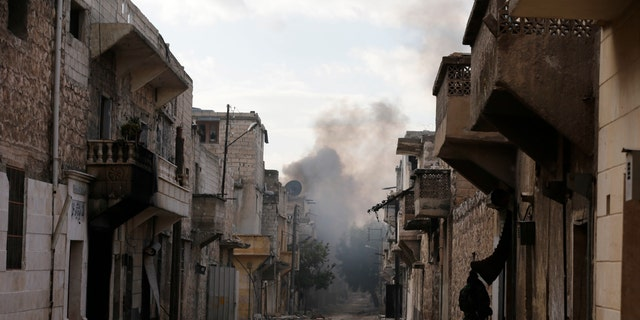 Smoke rises in east Aleppo after insurgent militants launch a mortar shell on government soldiers, Syria, Dec. 3.