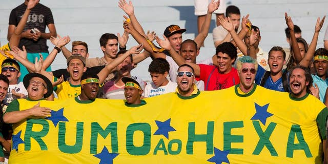 "Brazil's supporters cheer in the stands during a team practice session at the Serra Dourada stadium in Goiania, Brazil, Monday, June 2, 2014. The banner reads in Portuguese ""On its way to the sixth"", referring to Brazil's five past World Cup titles and hope for a sixth this year. Brazil will face Panama on Tuesday in preparation for the World Cup soccer tournament that starts on 12 June. (AP Photo/Andre Penner)"