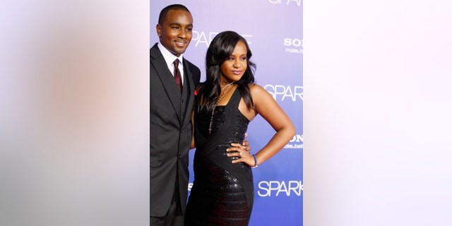 """Bobbi Kristina Brown, daughter of the late singer Whitney Houston, reveals a tattoo with the initials """"W H"""" as she waves while arriving with boyfriend Nick Gordon at the premiere of the new film """"Sparkle"""" starring Jordin Sparks and the late Whitney Houston in Hollywood August 16, 2012."""