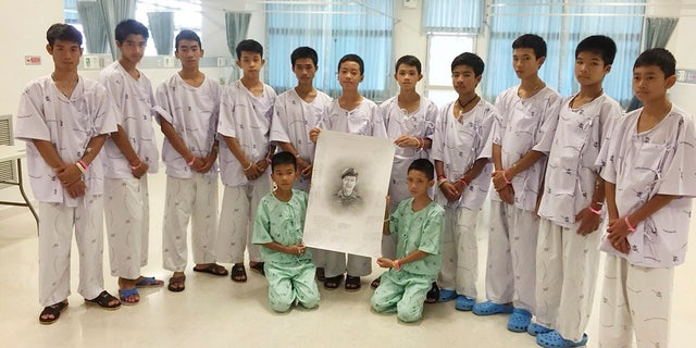 The rescued soccer team members pose with a sketch of the Thai Navy SEAL diver who died while trying to rescue them.