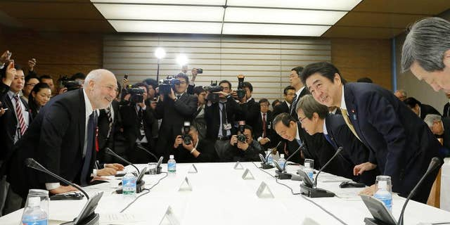 In this March 16, 2016 photo, Japanese Prime Minister Shinzo Abe, second from right, and Nobel laureate economist Joseph Stiglitz, left, take their seats for an economic seminar with other members of his Cabinet at Abe's official residence in Tokyo. The message: no matter how bad the debt, Japan's economy is too weak to withstand another tax hike. All is not well in Abenomics land, the world's third-largest economy, and Abe is seeking fresh advice from top experts, both foreign and Japanese, on what to do next. (Kazunari Fujikake/Kyodo News via AP) JAPAN OUT, MANDATORY CREDIT