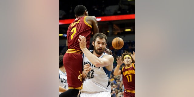 Cleveland Cavaliers' Kyrie Irving, left, gets off a pass to Anderson Varejao, right, of Brazil, as he runs into Minnesota Timberwolves' Kevin Love in the second half of an NBA basketball game Wednesday, Nov. 13, 2013, in Minneapolis. The Timberwolves won 124-95. Irving led the Cavaliers with 20 points. (AP Photo/Jim Mone)