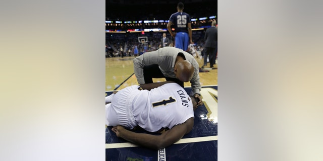 New Orleans Pelicans point guard Tyreke Evans (1) is tended to after coming down badly and hurting his ankle in the second half of an NBA basketball game against the Oklahoma City Thunder in New Orleans, Friday, Dec. 6, 2013. The Thunder won 109-95. (AP Photo/Gerald Herbert)