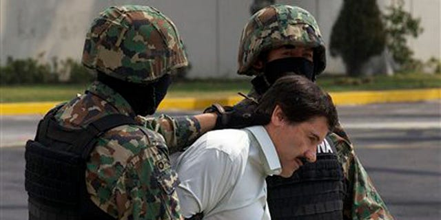"""Joaquin """"El Chapo"""" Guzman is escorted to a helicopter in handcuffs by Mexican navy marines at a navy hanger in Mexico City, Mexico, Saturday, Feb. 22, 2014."""