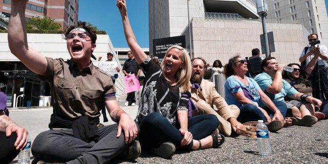 Protesters sat in the street on Monday in downtown Los Angeles to block entry to an ICE facility.