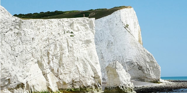 The edge of the cliff is fractured with cracks, and every year along the iconic white cliffs, hundreds of tonnes of rocks fall onto the beach below.