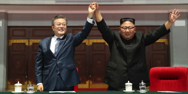 """South Korean President Moon Jae-in and North Korean leader Kim Jong Un raise their hands after watching the mass games performance of """"The Glorious Country"""" at May Day Stadium in Pyongyang, North Korea, Wednesday, Sept. 19, 2018. (Pyongyang Press Corps Pool via AP)"""