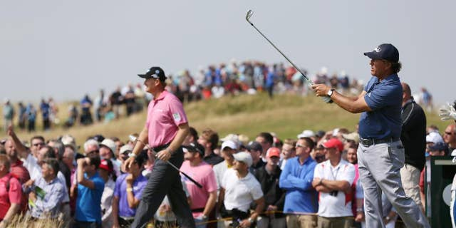 Phil Mickelson of the US plays his shot off the 9th tee box as Ernie Els of South Africa starts to walk along the fairway during the second day of the British Open Golf championship at the Royal Liverpool golf club, Hoylake, England, Friday July 18, 2014. (AP Photo/Scott Heppell)