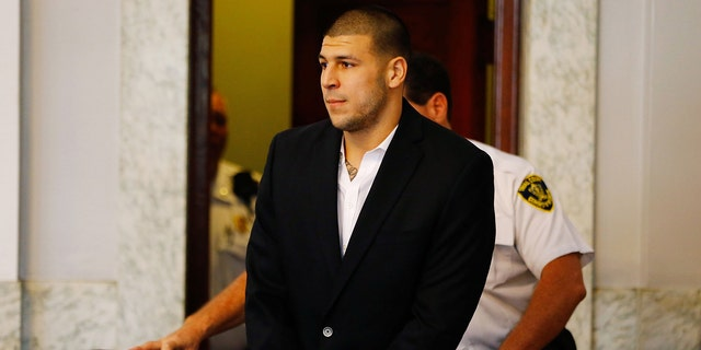 Aaron Hernandez is escorted into the courtroom on August 22, 2013 in North Attleboro, Massachusetts.