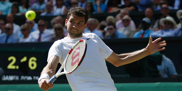 Grigor Dimitrov of Bulgaria plays a return to Novak Djokovic of Serbia during their men's singles semifinal match at the All England Lawn Tennis Championships in Wimbledon, London, Friday, July 4, 2014. (AP Photo/Pavel Golovkin)