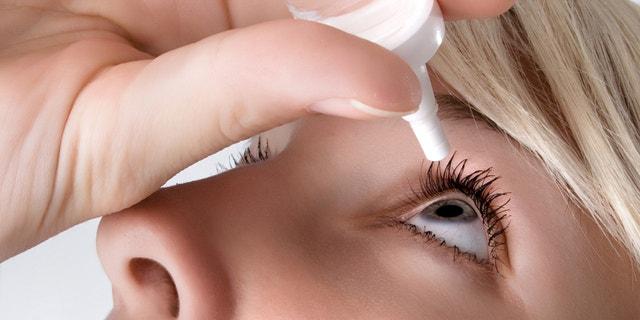 woman applying eyedroppes, close up