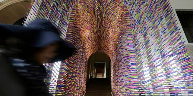 """A woman passes by an installation called """"Transition"""", made with lipstick packages, part of the Milan's Furniture Fair, in Milan, Italy, Monday, April 8, 2012. The 52nd International Furniture Fair (Salone del Mobile) opens in Milan on Tuesday, April 9, 2013 until April 14. (AP Photo/Luca Bruno)"""