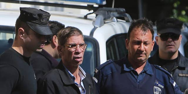 """EgyptAir plane hijacking suspect Seif Eddin Mustafa, second left, is escorted by Cyprus police officers as he leaves a court after a remand hearing as authorities investigate him on charges including hijacking, illegal possession of explosives and abduction in the Cypriot coastal town of Larnaca Wednesday, March 30, 2016. Mustafa described as """"psychologically unstable"""" hijacked a flight Tuesday from Egypt to Cyprus and threatened to blow it up. His explosives turned out to be fake, and he surrendered with all passengers released unharmed after a bizarre six-hour standoff. (AP Photo/Petros Karadjias)"""