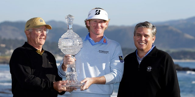 Brandt Snedeker poses with co-amateur champions Toby S. Wilt, left, and John Erickson, right, on the 18th green of the Pebble Beach Golf Links following the AT&T Pebble Beach Pro-Am golf tournament, Sunday, Feb. 10, 2013, in Pebble Beach, Calif. Snedeker won the tournament after shooting a 7-under 65. Wilt played with Snedker and Erickson was paired with Michael Letzig. (AP Photo/Eric Risberg)